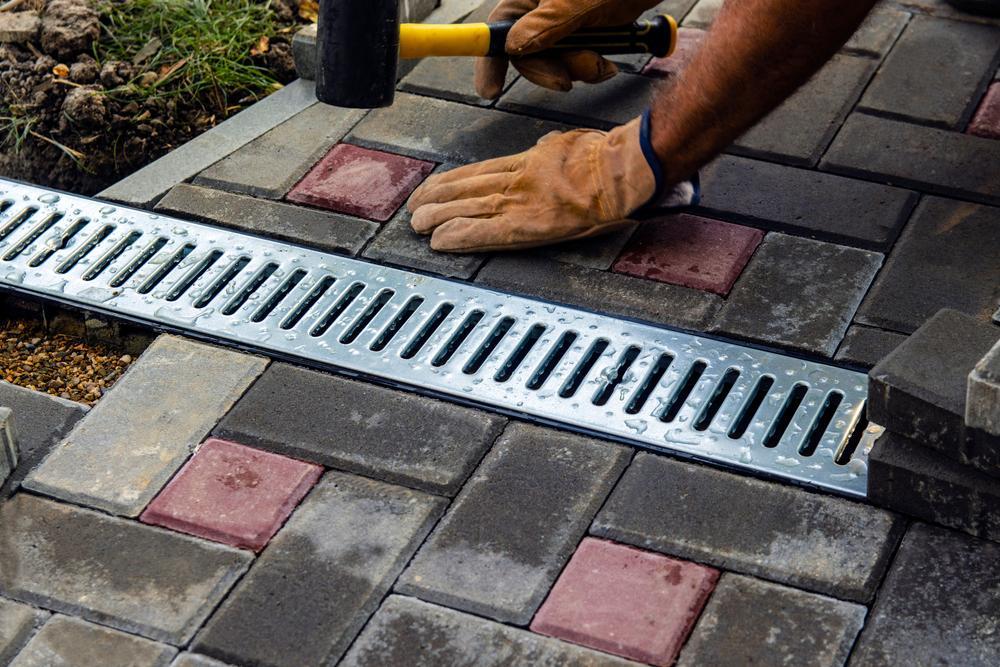 Man using rubber hammer on driveway bricks
